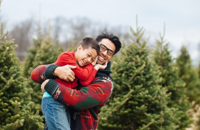 man carrying boy while standing and smiling near pine trees