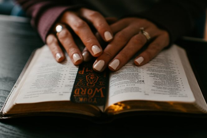 person wearing silver ring on ring finger on bible